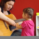 Young girl listens to teacher playing guitar