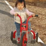 Young girl riding a red tricycle