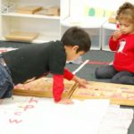 Two boys play together in the classroom