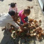 Students playing in the leaves at recess.