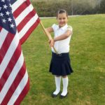 Montessorian student holding American flag