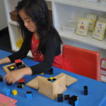 Young girl works with the trinomial cube in class