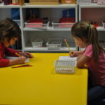 Two girls work hard on their classwork.
